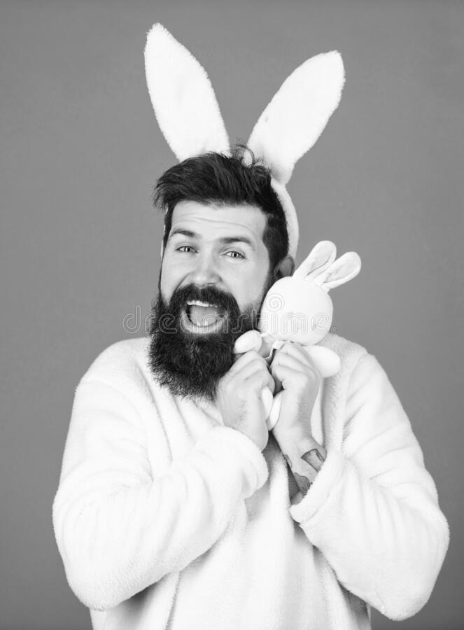 Man handsome face wear white bunny ears. Easter bunny. White bunny symbol of easter holiday. Soft and tender. Guy with stock photo