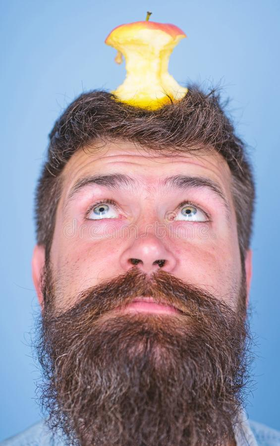Man handsome hipster long beard almost eaten apple stump on head as target. Live target concept. Hipster surprised face stock images