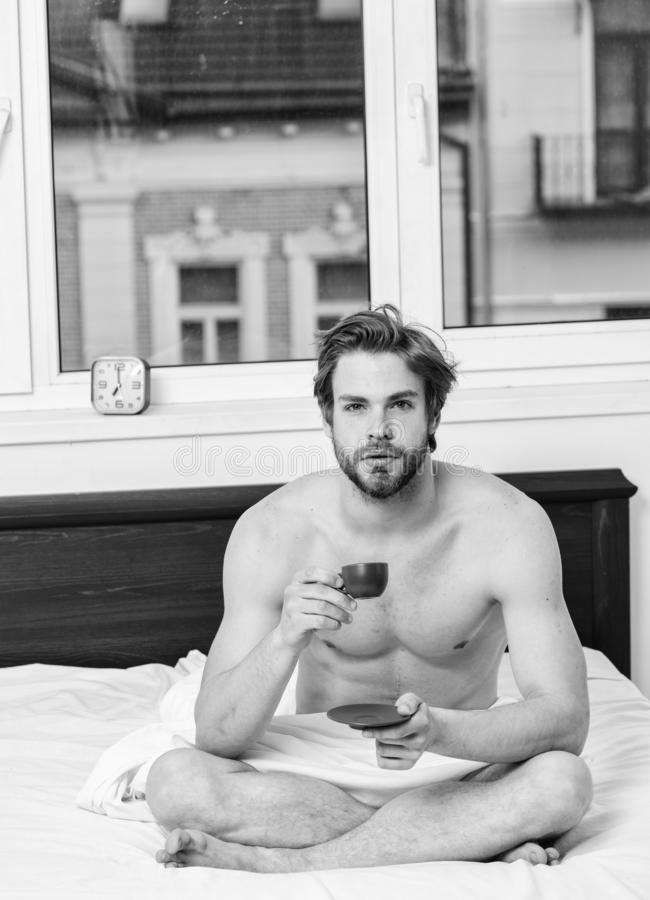 Man handsome macho with muscular torso relaxing on bed with cup of coffee. Coffee fills you with energy. Every morning stock photos