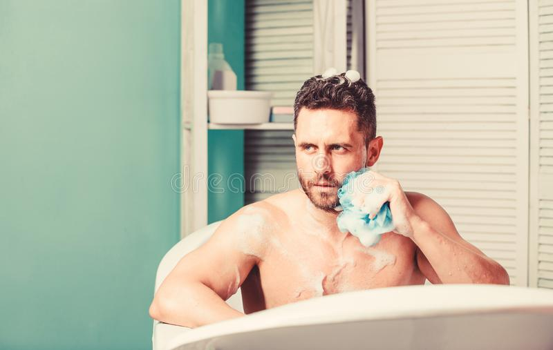 Man handsome muscular guy relaxing in bath. Spa wellness concept. Taking bath with soap suds. Treating yourself with hot stock images