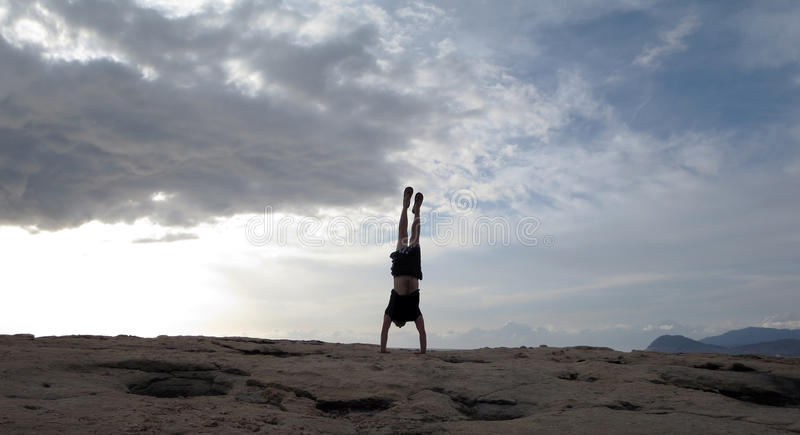 Man Handstands at on rocks of Ko Olina. Man wearing a hat, t-shirt, shorts, and slippers Handstands on shore rocks of Ko Olina on Oahu, Hawaii with dramatic stock photography
