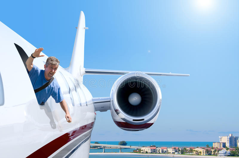 Man hanging out flying airplane window. A man is hanging out of a private jet airplane window with a smile on his face as he waves hello as the plane is flying stock images