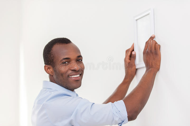 Man hanging picture frame. Cheerful young black man hanging picture frame and smiling at camera stock images