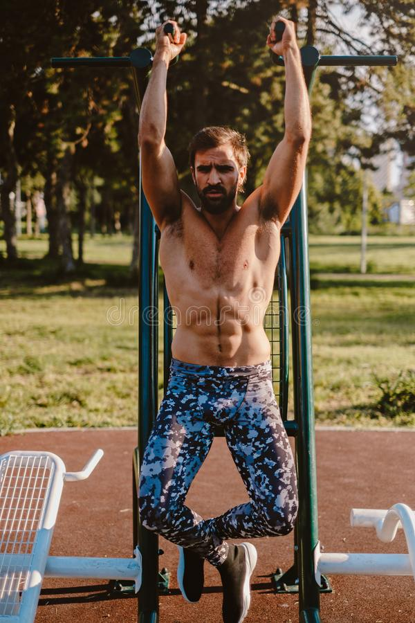 Man hanging from pull up bar royalty free stock photography
