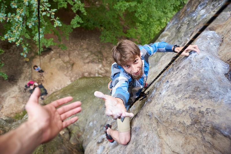Climber rock climbing overhanging cliff with rope. Asking for help. Man helping his friend to climb a rock. Man hanging on a rope on rock stretching out hand royalty free stock image
