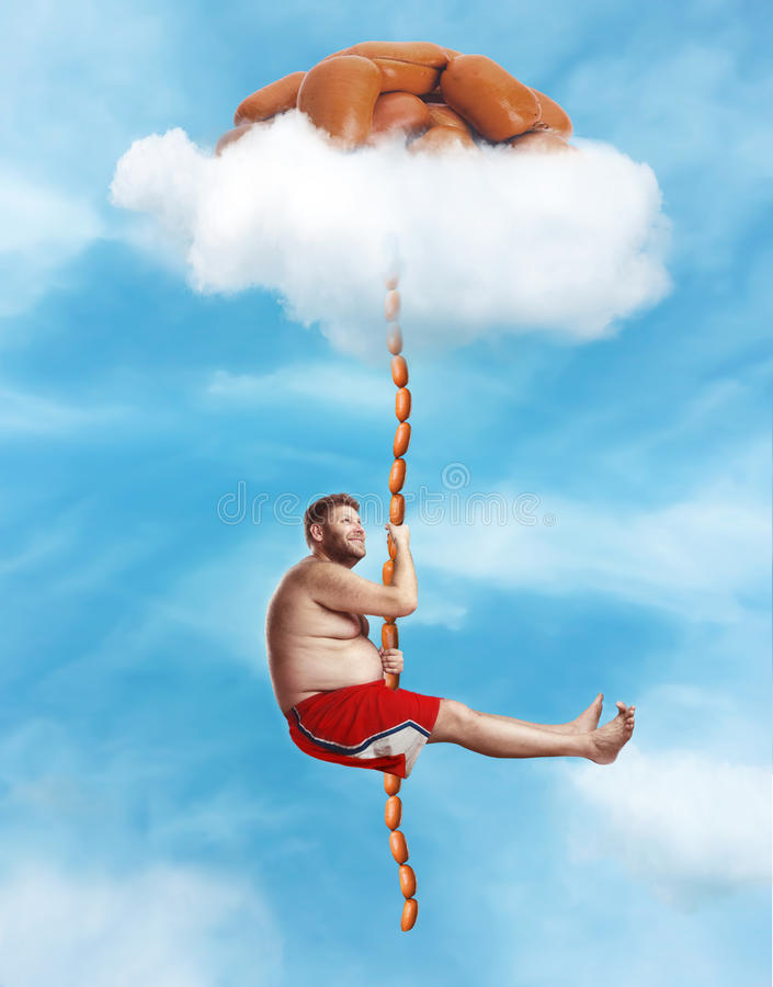 Man hanging on the sausage rope. Fat happy man hanging on the sausage rope in the sky stock image