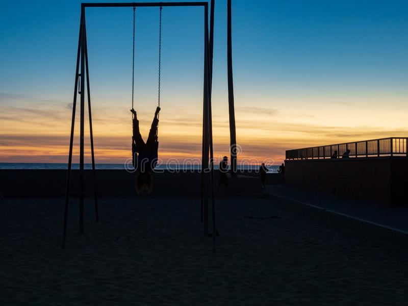 Man hanging upside down on gymnastic rings outdoors in the dusk sky on a beach stock images