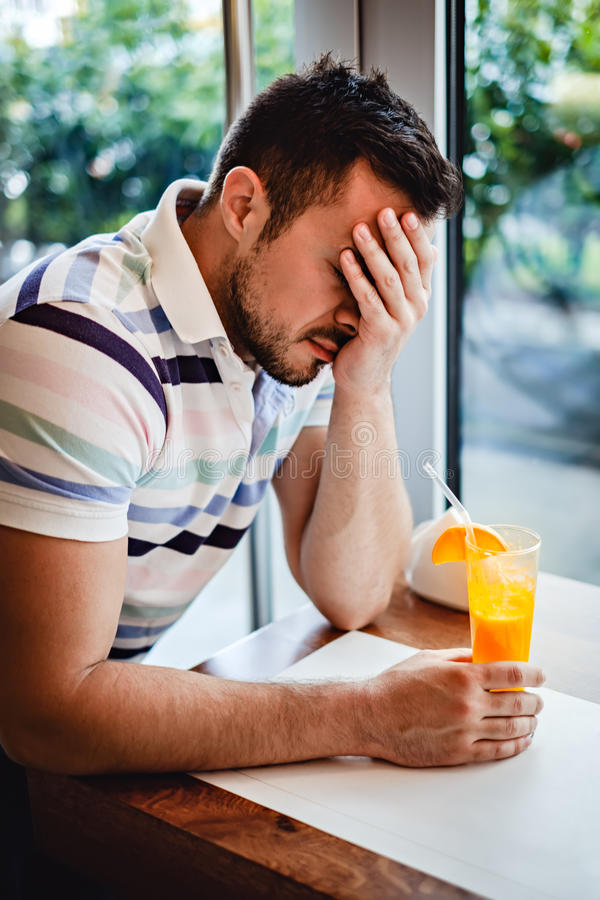 Man with hangover drinking orange juice in a cafe stock photography