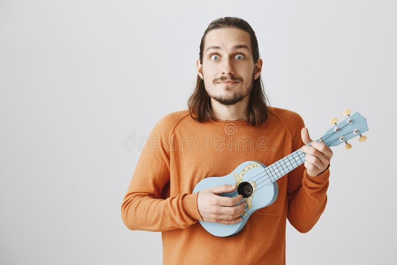 Man is happy finally learn new chord. Positive handsome guy with funny expression in orange sweater holding blue ukulele stock images