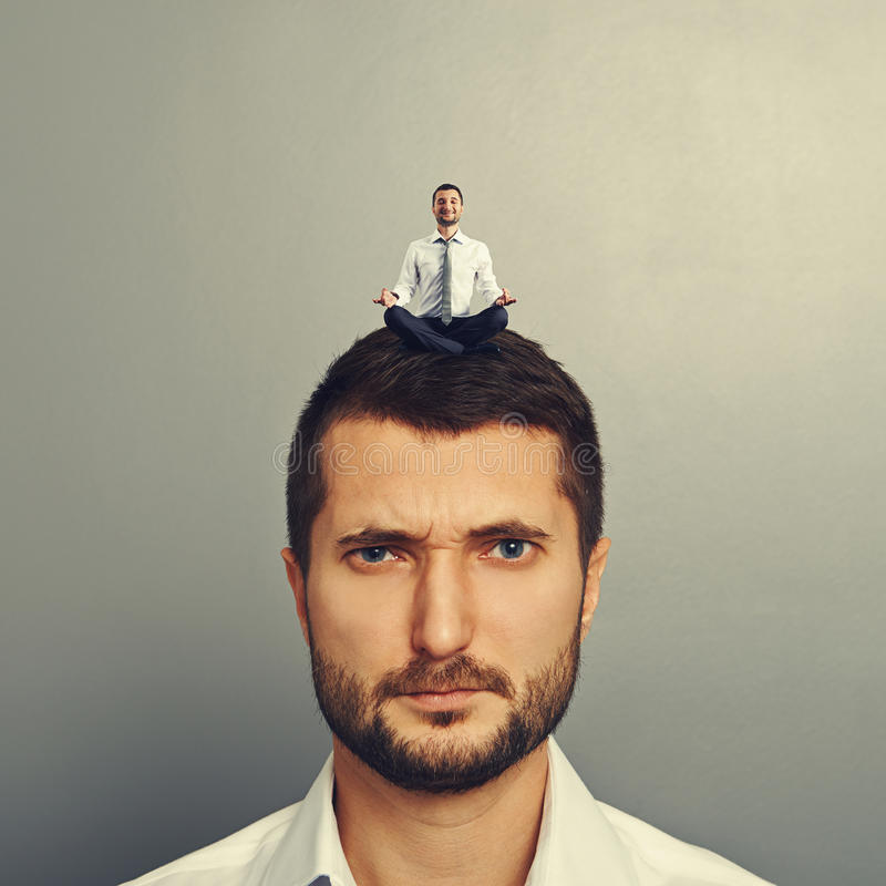 Man with happy man on the head. Displeased man with small happy man on the head royalty free stock images