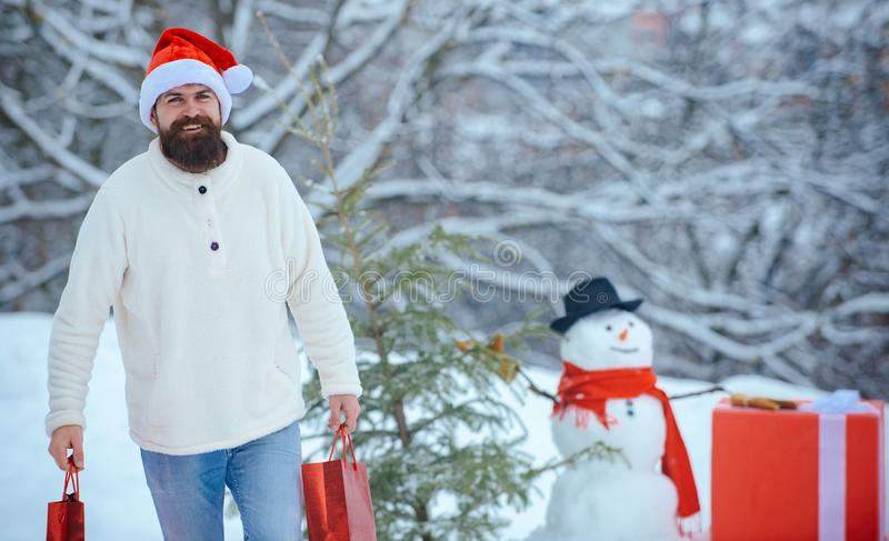 Man is happy about the new year. Santa wishes merry Christmas. Happy father playing with a snowman on a snowy winter stock photography