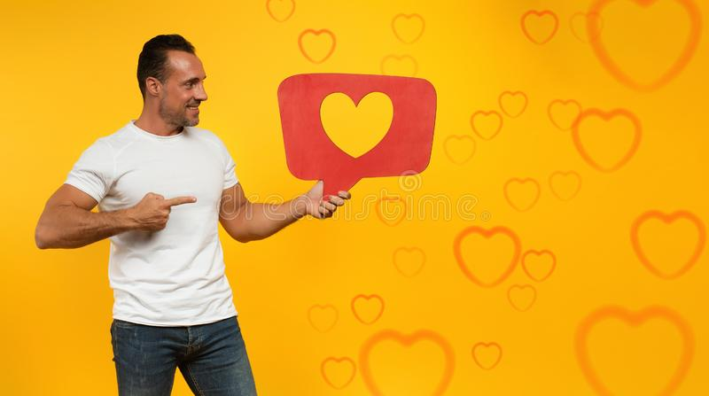 Man is happy because receives hearts on social network. Application stock photos