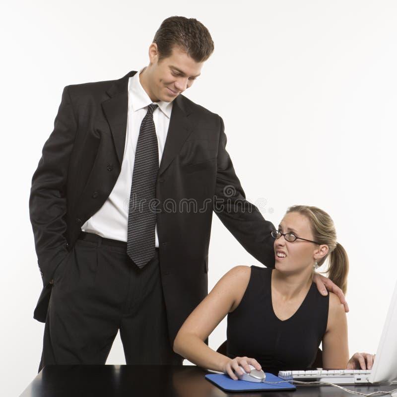 Man harassing woman at computer. Caucasian mid-adult man sexually harassing woman sitting at computer stock image