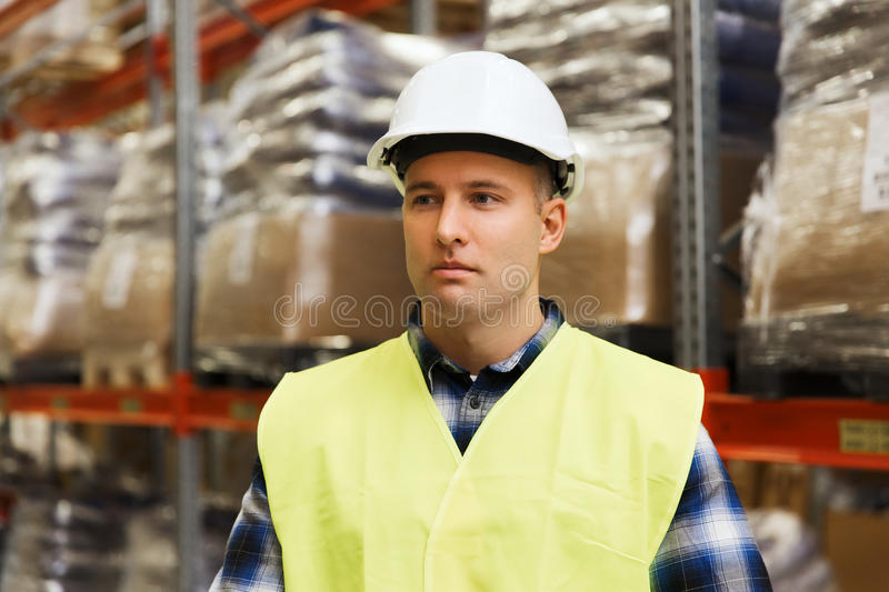 Man in hardhat and safety vest at warehouse. Wholesale, logistic, people and export concept - man in reflective safety vest and hardhat at warehouse stock images