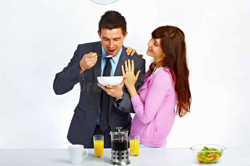 Man has breakfast before go to work. Businessman has breakfast before go to work and his wife standing near him and hugging him stock image