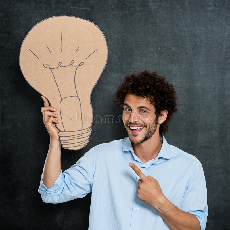 Man Has A Bright Idea. Portrait Of Young Man Showing Big Bulb Cardoard Symbol Over Gray Background royalty free stock photography