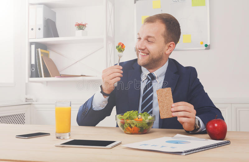 Man has healthy business lunch in modern office interior royalty free stock photos