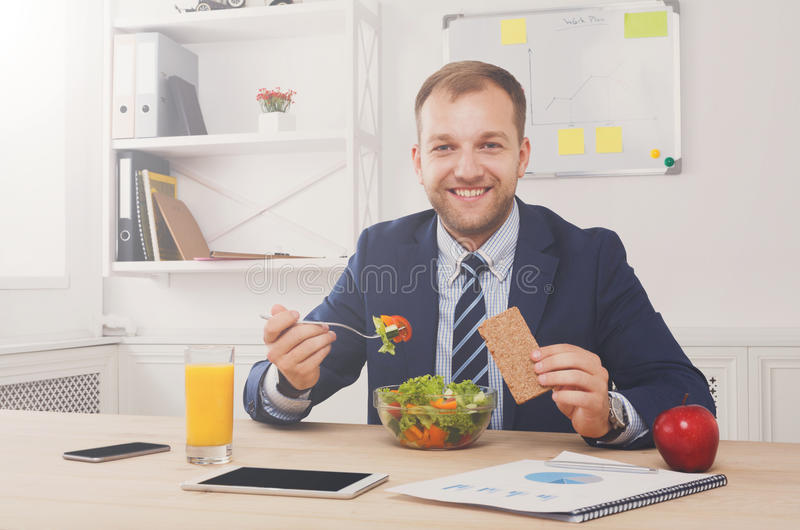 Man has healthy business lunch in modern office interior royalty free stock images