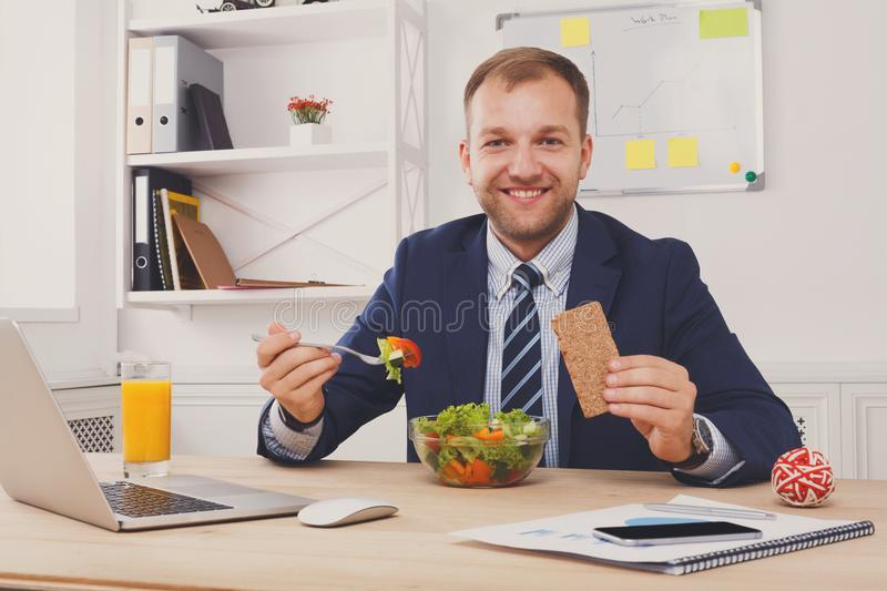Man has healthy business lunch in modern office interior stock photo