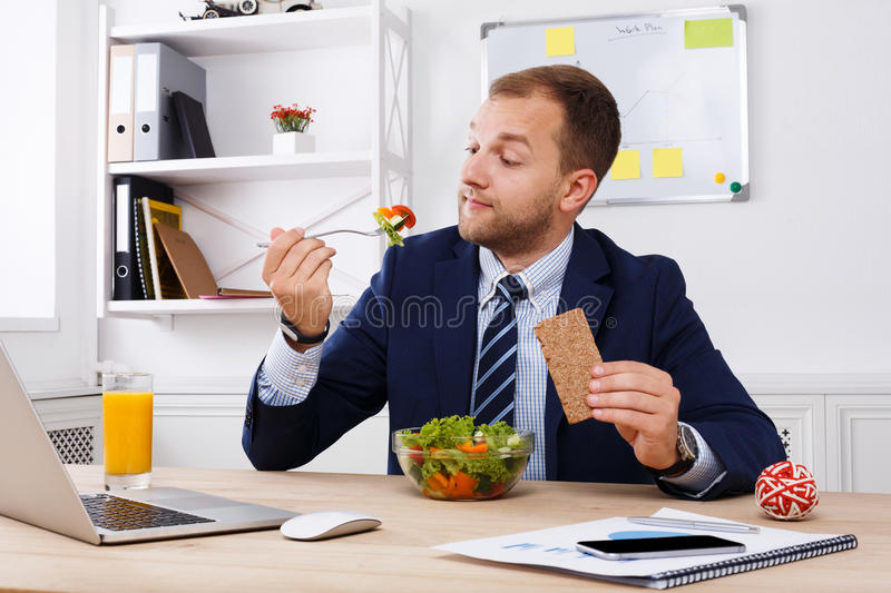 Man has healthy business lunch in modern office interior royalty free stock photography
