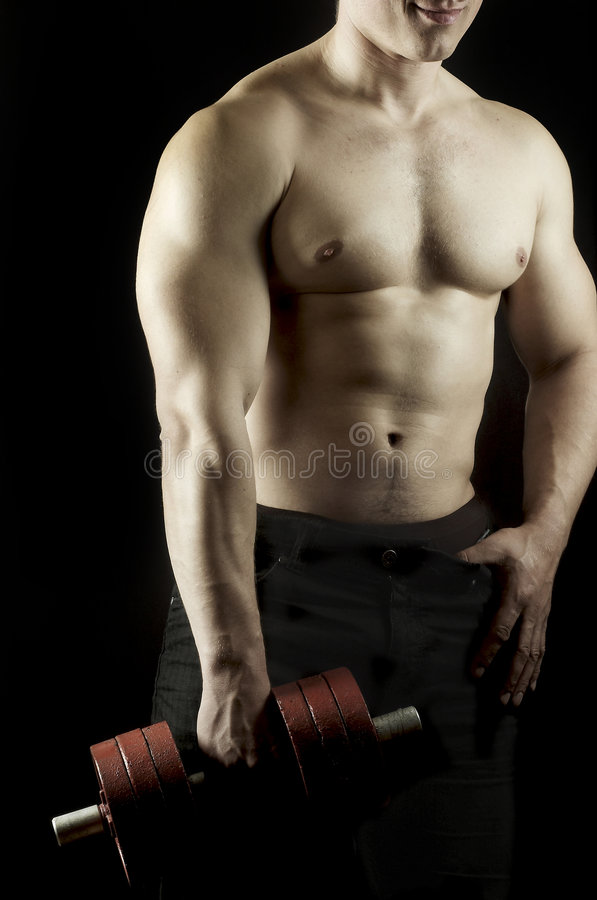 Man has lowered dumbbell. The young man of an athletic constitution plays sports royalty free stock images