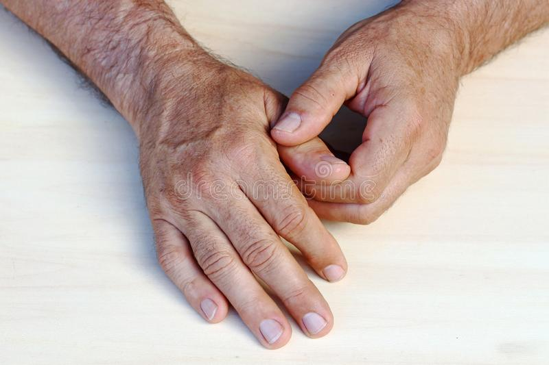 A man has pain in his hands and fingers royalty free stock photo