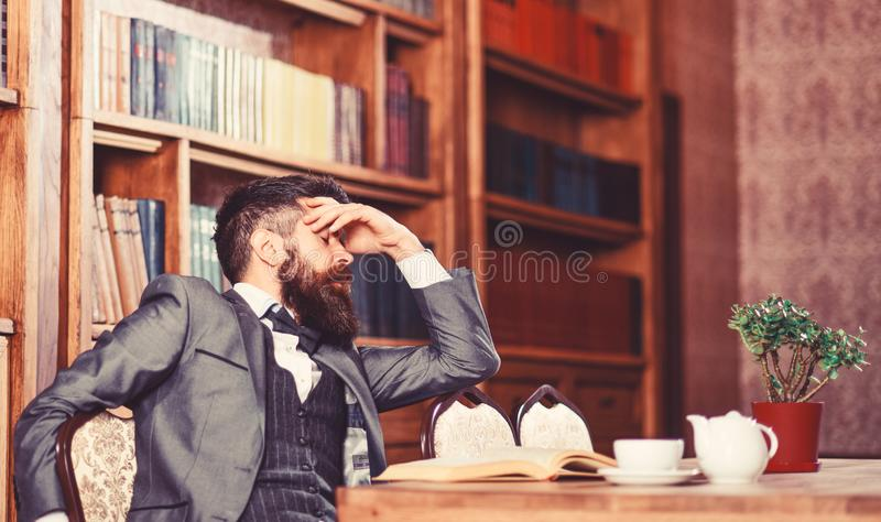 Man has terrible headache. Bearded man in formal suit suffers from negative thoughts and looks unsatisfaied. Mature man stock photography