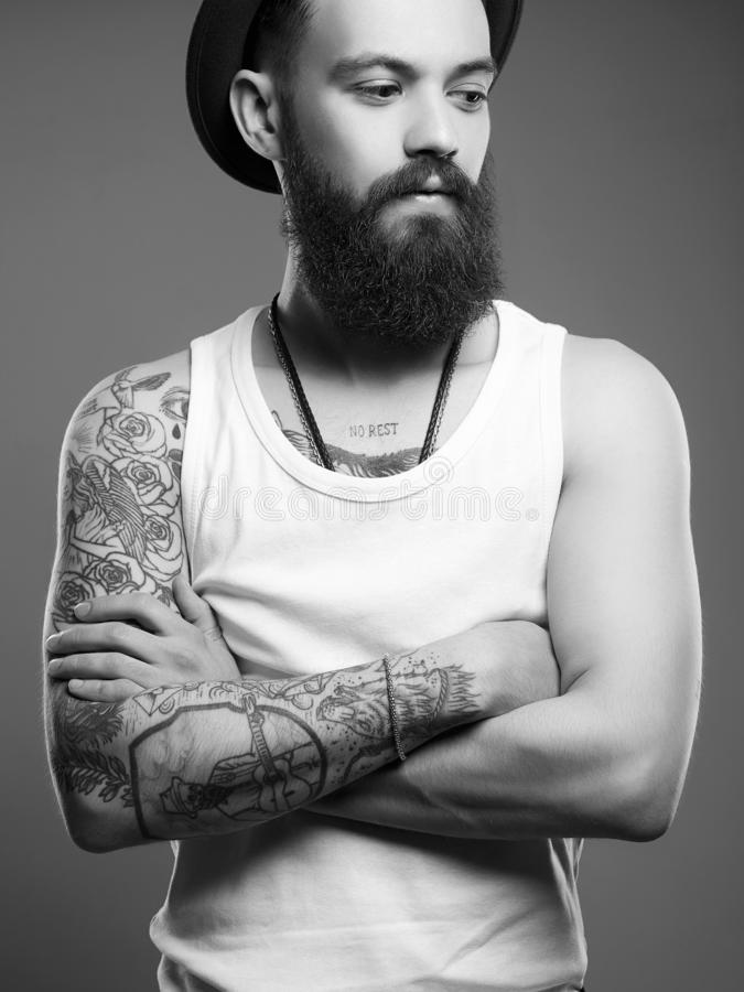 Man in hat. boy with tattoo. Black and white portrait. Tattooed handsome Man in Hat. Brutal hipster boy with tattoo. Black and white portrait royalty free stock photography