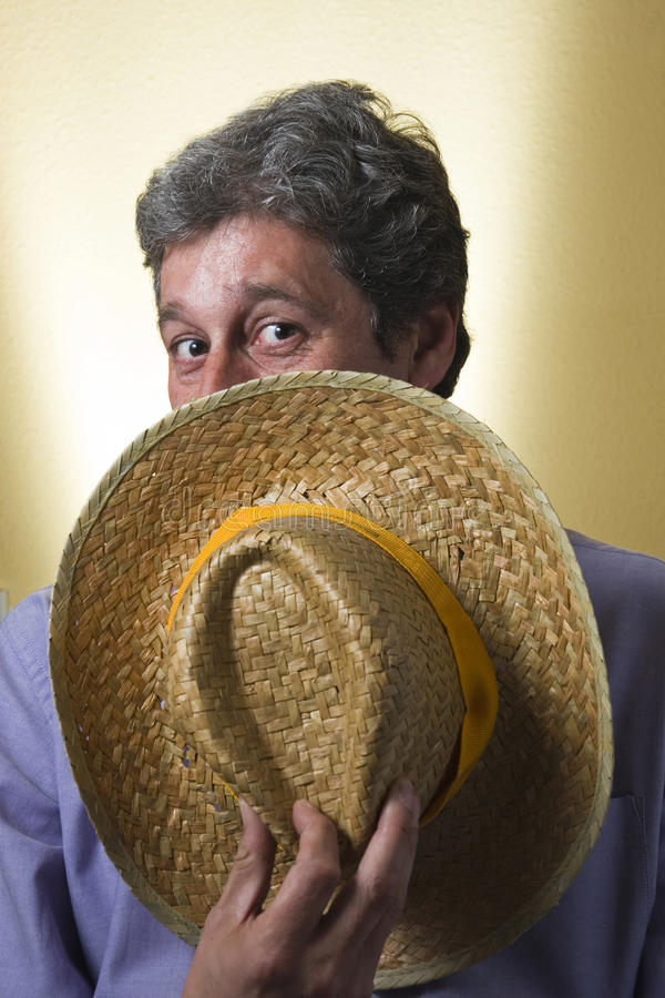 The man with the hat cap. Portrait of a man covered with a straw hat and looking joking accomplice above royalty free stock image