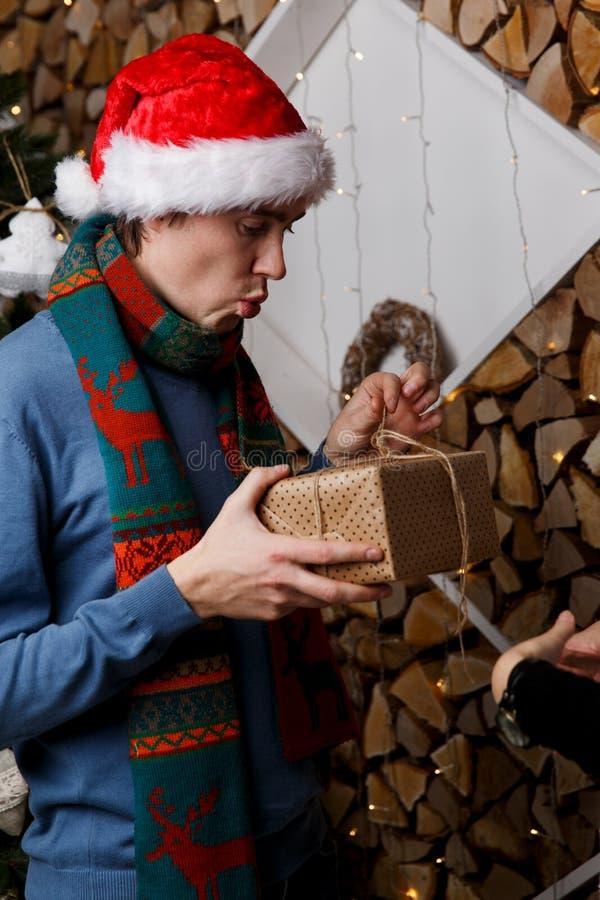 Man in hat opening gift. Man in Santa hat opening Christmas gift stock image