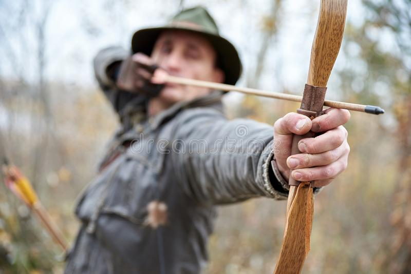 MAN IN THE HAT SHOOTS FROM WOODEN BOW ON OUTSIDE, stock image
