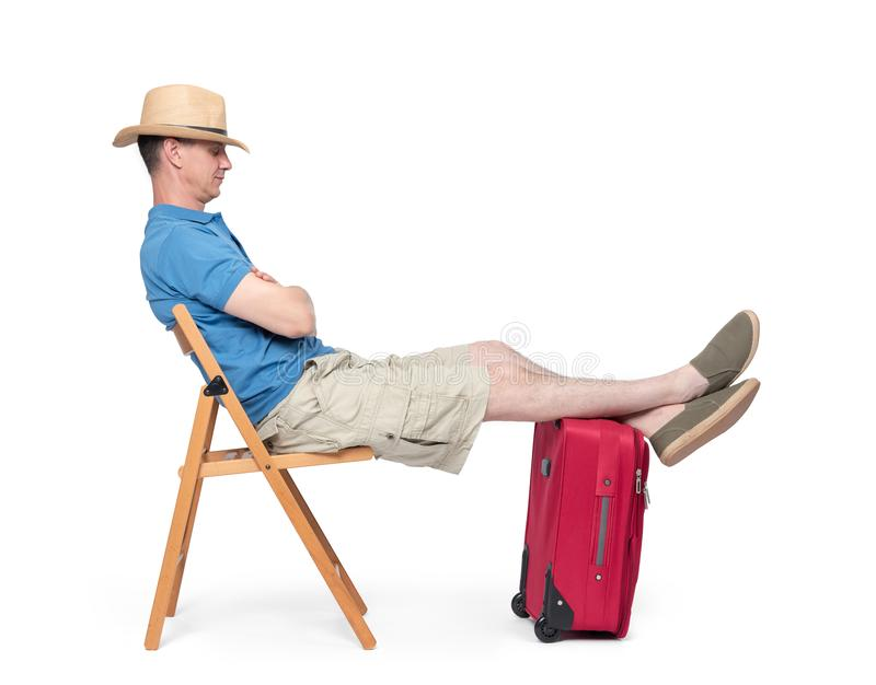 Man in a hat, shorts and a T-shirt, asleep sitting on a chair in anticipation, with his legs on a red suitcase. Isolated on white. Background royalty free stock images