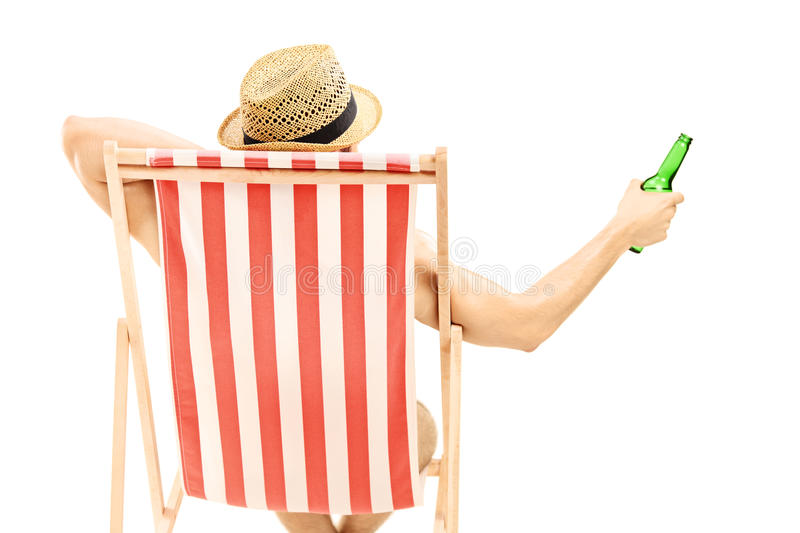 Download Man With Hat Sitting On A Beach Chair And Holding A Beer Bottle Stock Photo - Image: 31992976