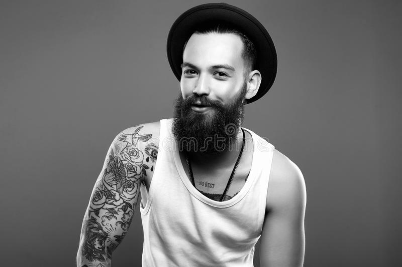 Man in Hat and Tattoo. Smiling Hipster boy. Fashion black and white Portrait of young bearded Man in Hat and Tattoo. Smiling Hipster boy. handsome man in hat stock photography