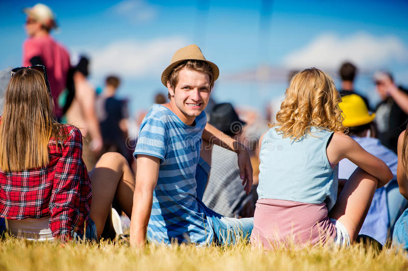Man with hat, teenagers, summer festival, sitting on grass. Man with hat, group of teenagers at summer music festival, sitting on the grass, back view, rear royalty free stock photography