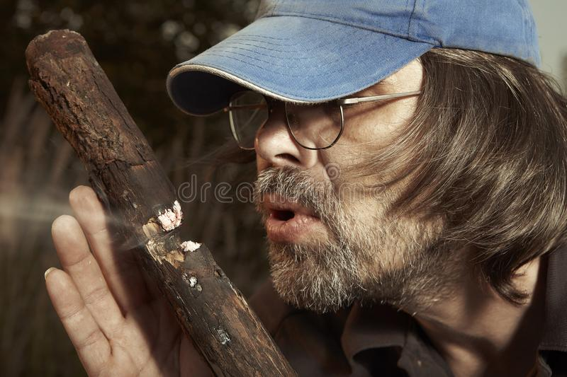Man camping in nature making fire with wood stick friction by hands. Man in hat trying to make a fire with wood stick friction stock images