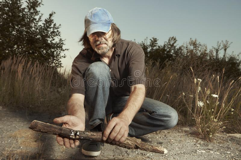 Man camping in nature making fire with wood stick friction by hands. Man in hat trying to make a fire with wood stick friction royalty free stock images