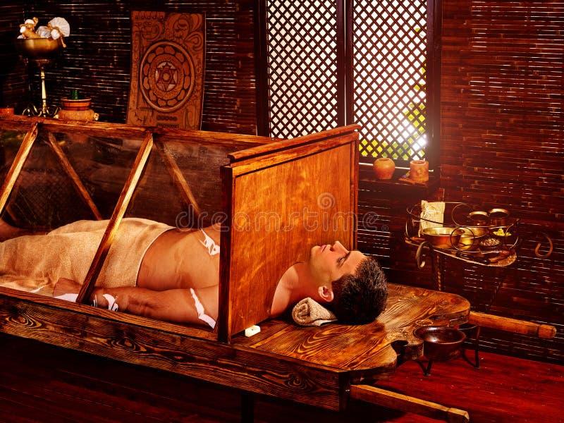 Man having Ayurvedic sauna treatment. Indian detoxification of male body. Man having Ayurvedic sauna treatment. Indian steam detoxification of male body. Study royalty free stock images