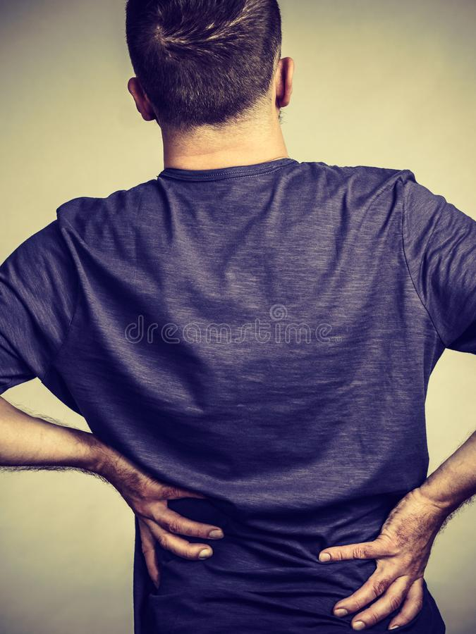 Man having back loins pain ache. View from back on man having terrible loins pain ache. Guy suffering from health problem royalty free stock photography