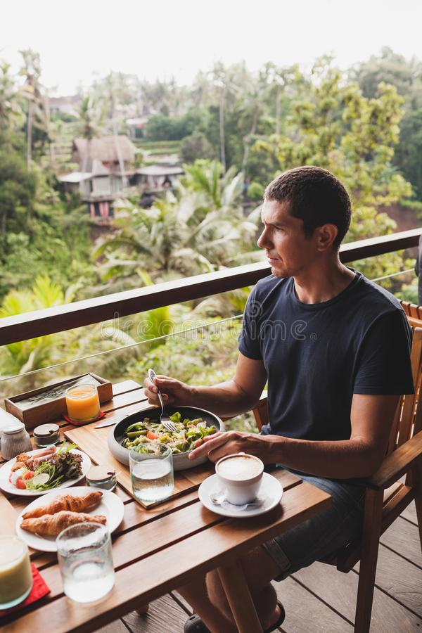Man having breakfast on terrace with jungle view stock image