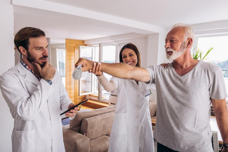 Man having chiropractic arm adjustment. Physiotherapy, sport injury rehabilitation. Senior men exercises in center for chiropractic stock images