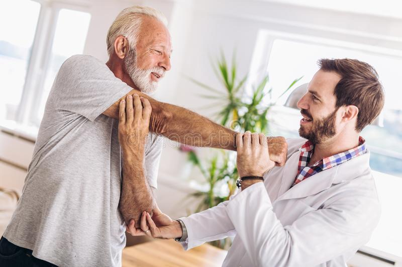 Man having chiropractic arm adjustment. Physiotherapy, sport injury rehabilitation. Senior men exercises in center for chiropractic royalty free stock photography