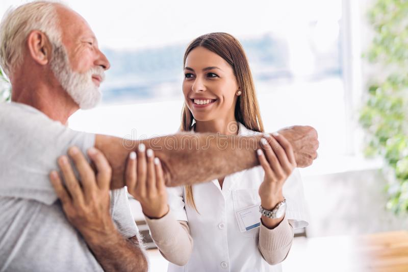 Man having chiropractic arm adjustment. Physiotherapy, sport injury rehabilitation. Senior men exercises in center for chiropractic royalty free stock photos