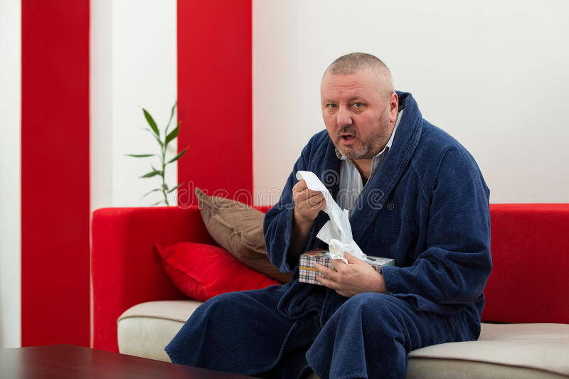 Man having a cold holding tissue with box full of tissues.  stock image