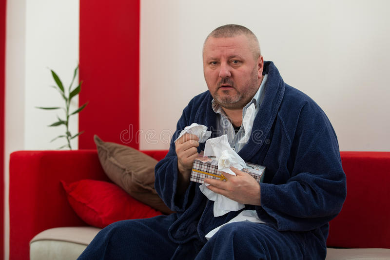 Man having a cold holding tissue with box full of tissues.  royalty free stock images