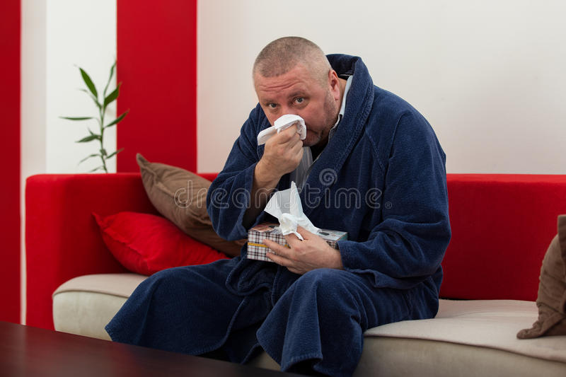 Man having a cold holding tissue with box full of tissues.  royalty free stock image