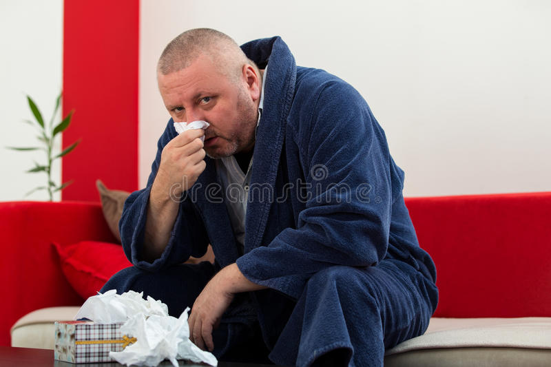 Man having a cold holding tissue with box full of tissues.  royalty free stock photos