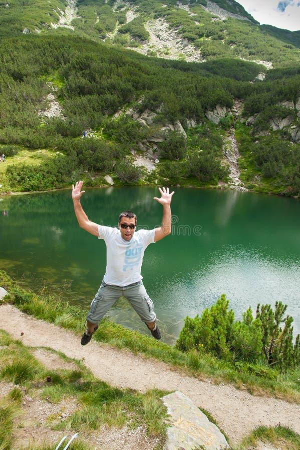 Man Having Fun on Mountain. Young manl jumping and having fun on Pirin mountain, Bansko, Bulgaria royalty free stock photography