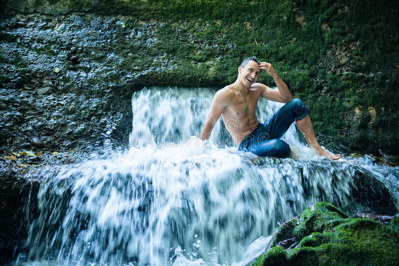 Man having fun and relax under waterfall. Happy young man having fun and relax under waterfall royalty free stock image
