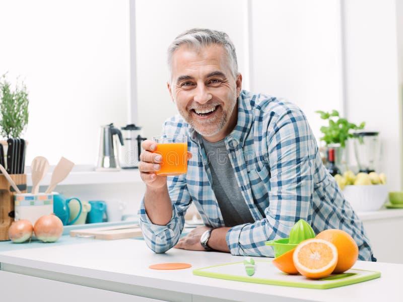 Man having a glass of fresh orange juice stock photos